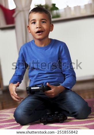 Cute Afro American boy playing video games at home.