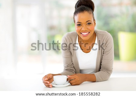 cute afro american woman drinking coffee at home - stock photo