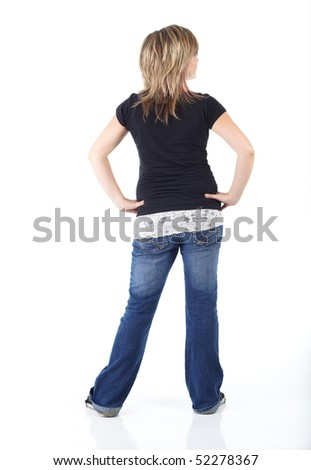 Cute and active young adult caucasian woman wearing a black top and blue jeans and with short brunette hair on a white background. Not Isolated