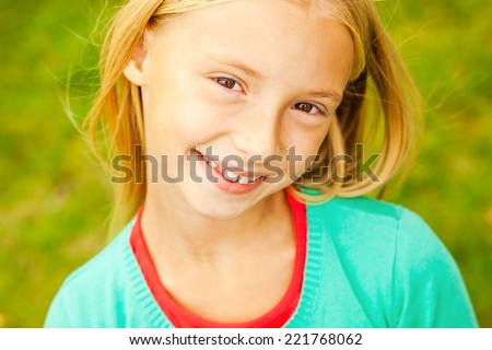 Cute and candid. Top view of cute little girl looking at camera and smiling while standing outdoors - stock photo