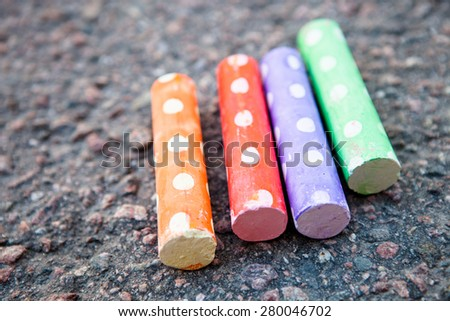Cute and colorful street chalk on asphalt outdoors - stock photo