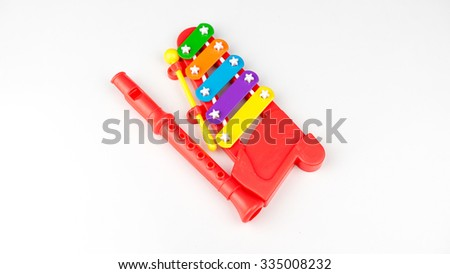 Cute and colourful mini flute and xylophone. 5 note music instrument for children musical education. Isolated on white background. Slightly de-focused and close-up shot. Copy space. - stock photo