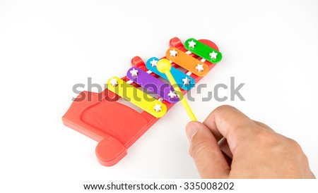 Cute and colourful mini xylophone. 5 note music instrument for children musical education. Isolated on white background. Slightly de-focused and close-up shot. Copy space. - stock photo