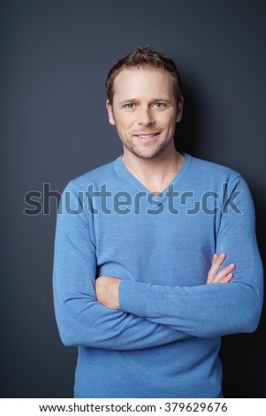 Cute and confident smiling young man in blue shirt with stubble on face and folded arms in front of dark background