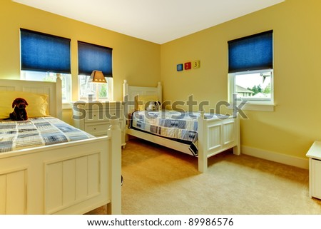 Cute and cozy kids bedroom in yellow and blue. - stock photo