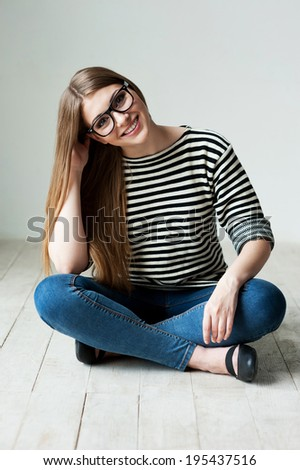 Cute and flirty. Beautiful young woman in striped clothing sitting on the hardwood floor and holding hand on chin - stock photo