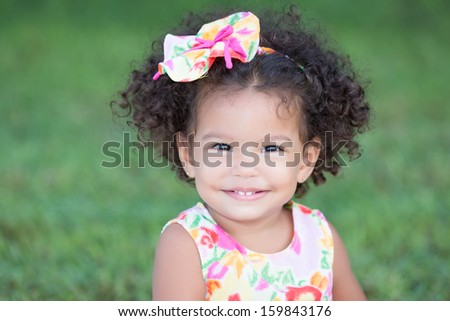 Cute and funny latin girl wearing a colorful flowers dress and  smiling with a diffused green grass background - stock photo