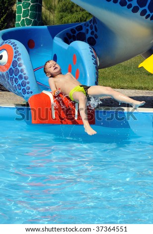 Cute and funny  little boy sliding down a water slide