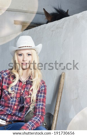 Cute and Happy Cowgirl Sitting in Cattleshed. Lighting Effects Used. Vertical Image - stock photo