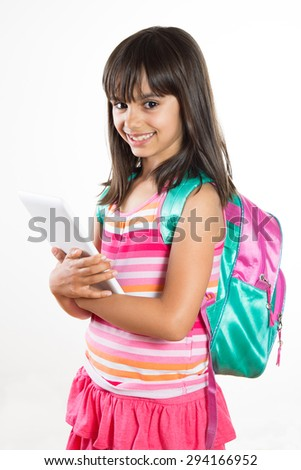 Cute and happy young school girl with schoolbag holding a tablet. Isolated on white - stock photo