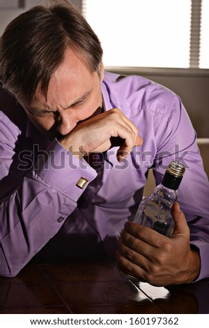 Cute and sad young man drinks whiskey at table - stock photo