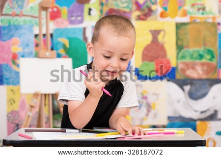 Cute and serious toddler boy is at the Art class. Looking down and painting with gray felt pen. Colorful wall and easel in background.