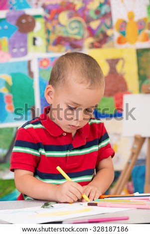 Cute and serious toddler boy is at the Art class. Looking down and painting with yellow felt pen. Colorful wall and easel in background.