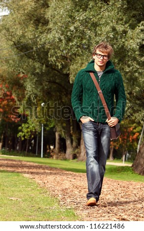 Cute and smart guy walking at cold autumn day in sunny park - stock photo