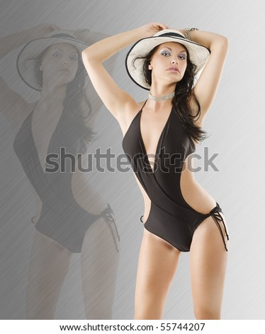 cute and stunning brunette woman in black swimsuit and wet hair wearing an hat - stock photo