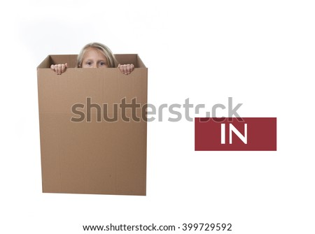 cute and sweet blond hair child hidden in cardboard box isolated on white background  in learning english prepositions and words language card set for education school textbook  - stock photo