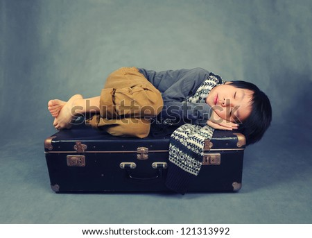 Cute and tired boy sleeping on suitcase - stock photo