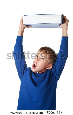 Cute angry blond boy in a blue sweater holding a very big blue book above wanting to throw it as a way of protest (isolated on white background) - stock photo