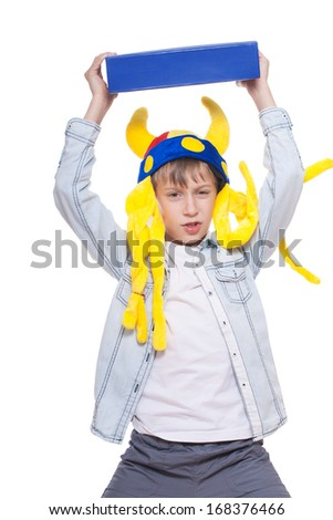 Cute angry stylish child wearing funny hat holding a very big blue book above with a menacing look (isolated on white background) - stock photo