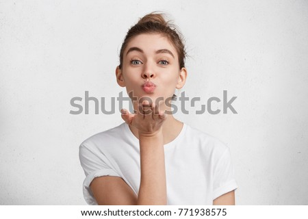 Cute appealing female blows kiss at camera, demonstrates love to boyfriend or says goodbye on distance, isolated over white studio background. Attractive young woman shows sympathy to someone