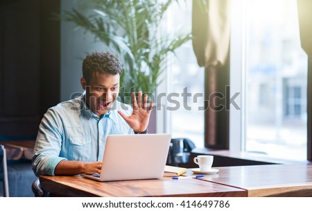 Cute Arabian guy is using computer for communication - stock photo