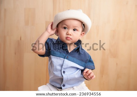 Cute asian baby boy holding hat. Portrait of adorable little child  - stock photo