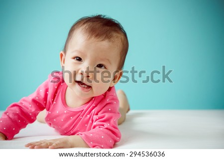 Cute Asian baby girl lying on stomach on bed, studio shot - stock photo