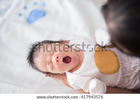 Cute asian baby newborn looking at grand mom  - stock photo