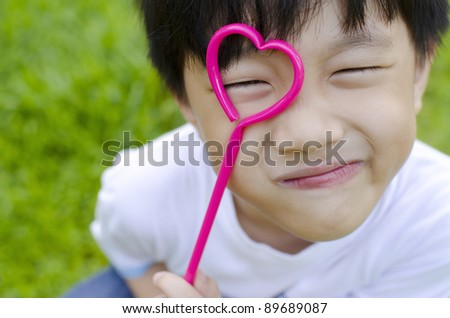 Cute Asian boy holding a heart shape on his eye - stock photo
