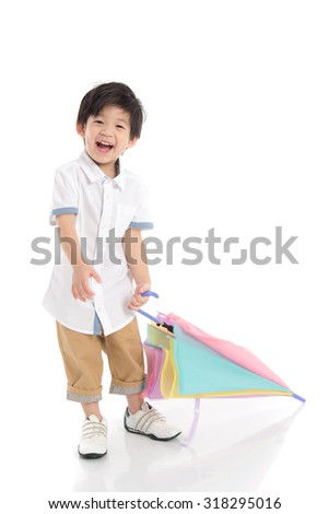 Cute asian boy holding umbrella on white background isolated