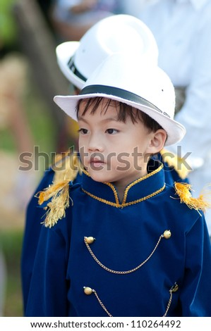 Cute asian boy in bright blue shirt and white hat portrait in sport day.