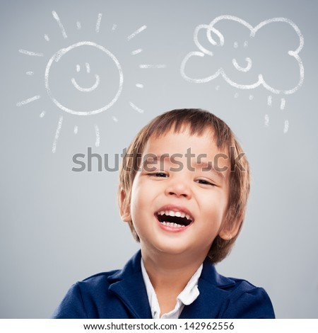Cute Asian boy laughing with children's drawings above his head. - stock photo