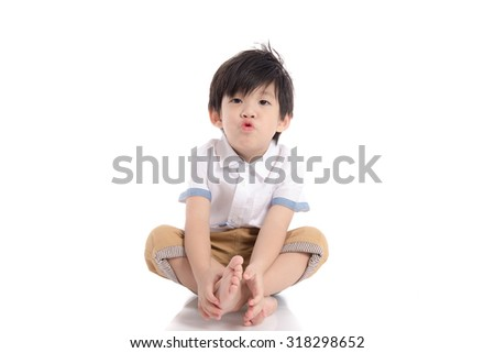Cute asian boy sitting on white background isolated