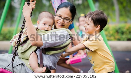 Cute Asian Caucasian mixed race toddler pushing his mother and brother together on a swing in a playground outside in the summer sun - stock photo