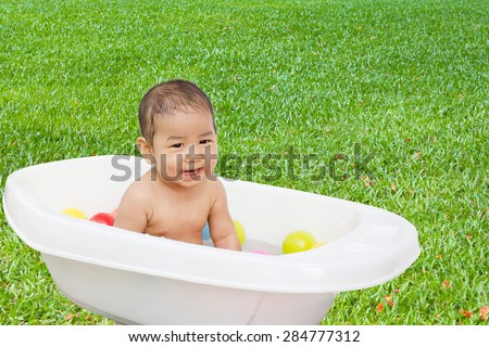 Cute asian child bathing in the garden