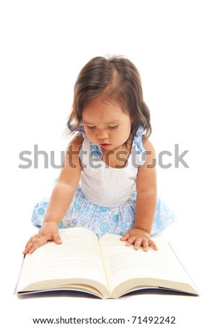 Cute asian child girl looking at book .