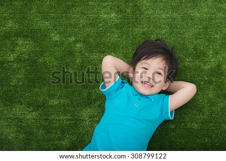 Cute asian child lying on green grass - stock photo