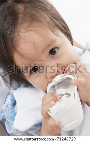 Cute asian child with shoes in the mouth .