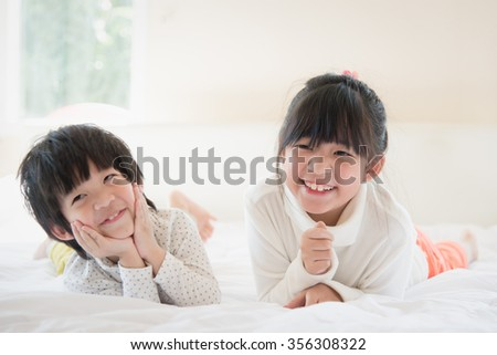 Cute asian children lying on white bed - stock photo