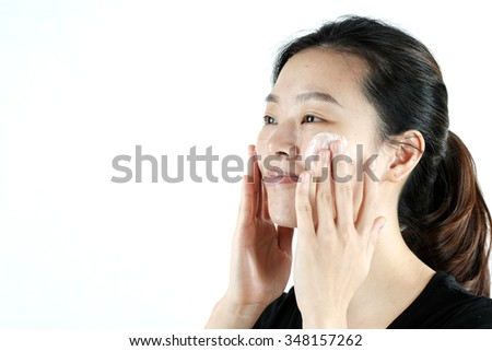 Cute asian girl applying cream lotion on face, isolated on white background