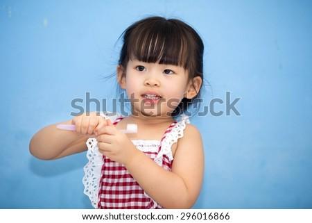 Cute Asian Girl brushing teeth.            - stock photo