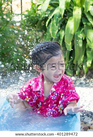 Cute asian girl is playing water  in her little plastic basin on Songkran festival (New year) in Thailand. - stock photo