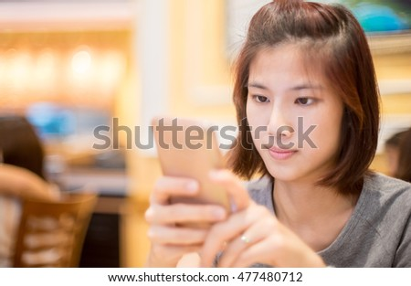 Cute Asian girl is using a mobile phone in cafe.