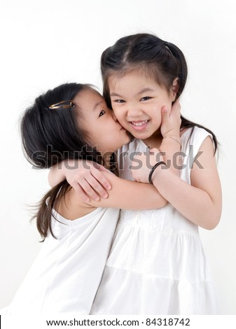 cute asian girl kissing her sister - stock photo