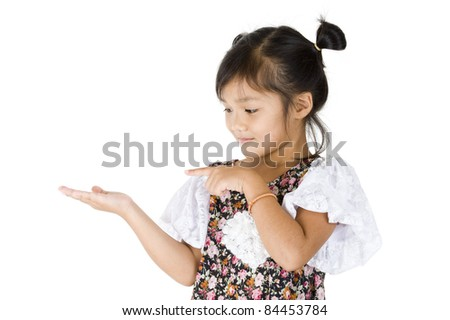 cute Asian girl looking and pointing at something in her hand, isolated on white background - stock photo