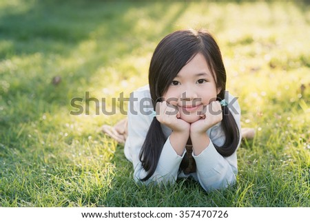 Cute asian girl lying on green grass - stock photo