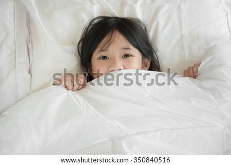 Cute asian girl lying under blanket on white bed - stock photo