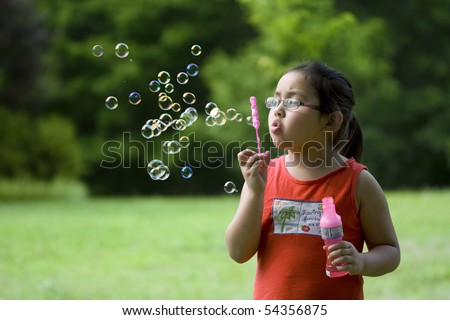 Cute Asian girl outside blowing bubbles - stock photo