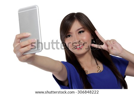 Cute Asian girl smile and make victory sign while taking a self shot photo with her smartphone camera, isolated on white background - stock photo