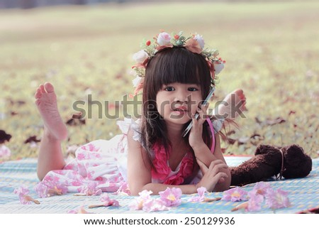 Cute Asian girl smiling and talking on her cell phone in the park, Vintage Tone